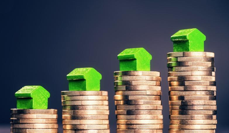 Model houses sitting on top of pound coins